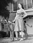 Young woman standing with her Great Dane in a courtyard — Stock Photo