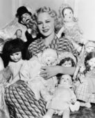 Portrait of a woman surrounded by dolls and smiling — Stock Photo