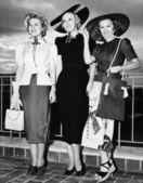 三个年轻的妇女站在一边的另一边,微笑着 — 图库照片