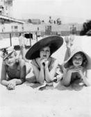 Porträtt av tre unga kvinnor ligga på stranden — Stockfoto