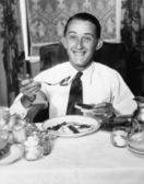 Young man having breakfast and smiling — Stock Photo