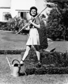 Profile of a young woman carrying a rake on her shoulder in a garden — Stock Photo