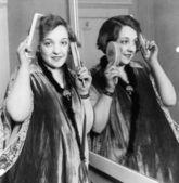женщина расчесывает и чистки зубов ее волосы — Стоковое фото