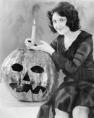 Young woman holding a burning candle on a Jack O' Lantern and smiling — Stock Photo