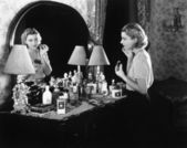 Young woman in front of her vanity applying make-up — Stockfoto