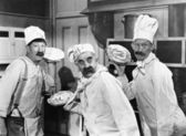 Three chefs holding pies for a fight in the kitchen — Стоковое фото