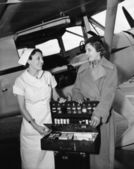 Female nurse with a young woman standing in front of an airplane and opening a medicine box — Stock Photo