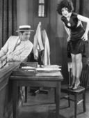 Young woman standing on a chair with a young man looking at her legs — Stock Photo