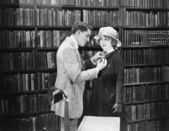 Profile of a young man attaching a brooch on a young woman's overcoat in a library — Stock Photo