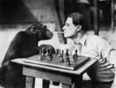 Profile of a young man and a chimpanzee smoking cigarettes and playing chess — Stock Photo