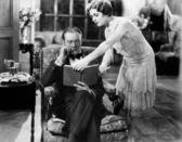 Profil młodą kobietę, pokazywanie książki człowiek siedzący na fotelu — Zdjęcie stockowe