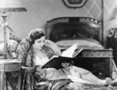 Young woman reclining in an armchair and reading a book in her bed room — Stock Photo