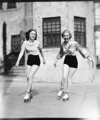 Two young women roller skating on the road and smiling — Stok fotoğraf