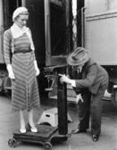 Profile of a man measuring weight of a woman standing on a weighing scale in front of a train — Stok fotoğraf