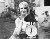 Portret van een jonge vrouw met een gewicht van haar puppy op een weegschaal — Stockfoto