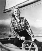 Bir yelkenli yönetiminde duran ve direksiyonu tutan genç bir kadın — Stok fotoğraf