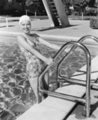 Jovem mulher subindo a escada de uma piscina — Fotografia Stock