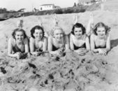 Portrait of five young women lying on the beach and smiling — Stock Photo