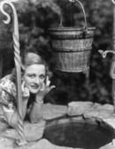 Porträt einer frau, stützte sich auf einen brunnen mit ihrem finger gekreuzt — Stockfoto