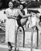 Profile of a young woman sitting on a ladder at the pool side with another woman standing behind her — Stok fotoğraf