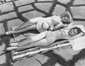 High angle view of two young women lying on a towel in the sun — Stock Photo