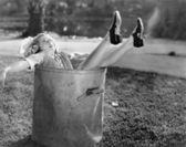 Woman fallen in the garbage bin at the roadside — Stock Photo