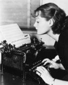 Profile of a young woman typing musical notes with a typewriter — Stock Photo