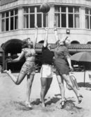 Three young women playing with a ball on the beach — Stock Photo