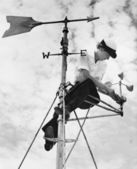 Low angle view of a young woman mending a weather vane — Stock Photo