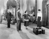 Four standing in a the lobby of a hotel with luggage — Stock Photo