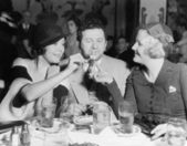 Two women lighting a cigarette for a man — Stock Photo