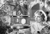 Woman looking into a bird cage with birds — Stock Photo