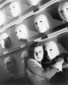 Woman looking frightened holding onto one mask on the wall of masks — Stock Photo