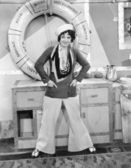 Woman in a sailors outfit in front of a life preserver — Stock Photo
