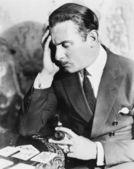 Mann hält ein rohr und ein kartenspiel in erwägung — Stockfoto