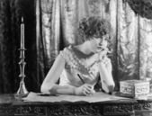 Young woman sitting at a desk with a pen in hand, looking sad while writing a letter — Stock Photo
