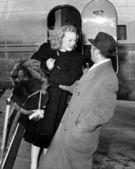 Frau heraustreten aus einem flugzeug wird von einem mann begrüßt — Stockfoto