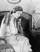 Young woman sitting on her bed in the bed room, speaking on the telephone — Stock Photo