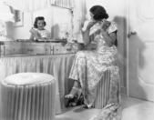 Young woman sitting in front of her vanity doing her hair — Stock Photo