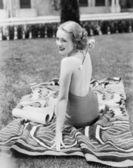 Giovane donna seduta in un vestito di sole su un prato, grattandosi la schiena — Foto Stock