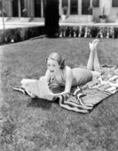 Young woman lying on a towel in her yard sunbathing and reading — Stock Photo
