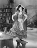 Young woman with a buccaneer hat dancing on a chair — Stock Photo