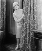 Young woman looking surprised behind a curtain — Stock Photo