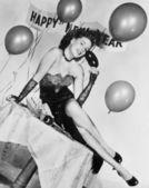 Mujer joven sentada en una mesa con globos y cartel — Foto de Stock