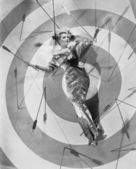 A target of desire, a young woman lying on the bulls eye with arrows around her — Stock Photo