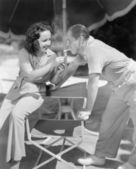 Woman giving a man a light for his cigarette — Stockfoto