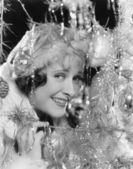 молодая женщина, глядя сквозь ветви рождественская елка с украшениями — Стоковое фото