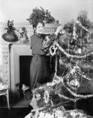 Junge frau, die einen weihnachtsbaum schmücken — Stockfoto