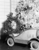 Little boy at Christmas sitting in his toy car — Stock Photo