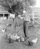 Jonge vrouw verkleed als een landbouwer voedsel om de kip — Stockfoto